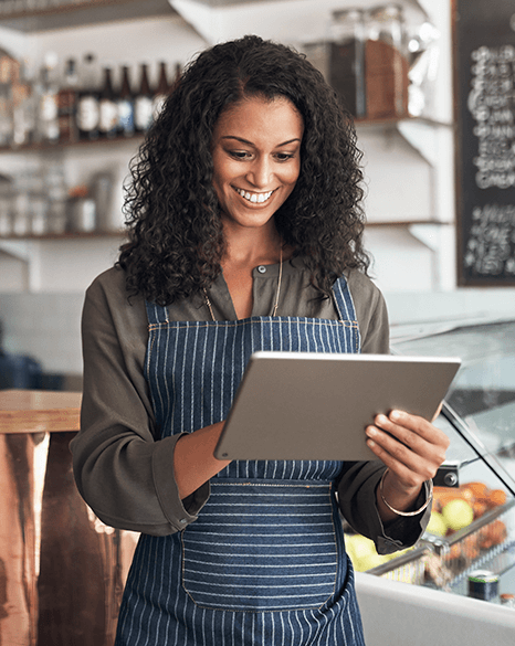 Woman working in a restaurant taking an order uisng a tablet device - Plusnet Business