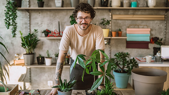 Man working in a florist standing behind three potted plants.
